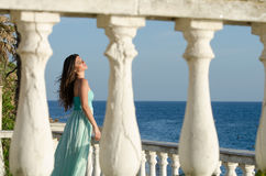 Lady standing on veranda of a beachfront home. Beautiful lady standing on veranda of a beachfront home, wearing a long blue dress, having a great time of her Royalty Free Stock Photography
