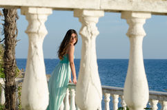 Lady standing on veranda of a beachfront home. Beautiful lady standing on veranda of a beachfront home, wearing a long blue dress, having a great time of her Royalty Free Stock Photos
