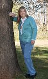 Lady stands by the tree smiling. Pretty lady stands by the tree posing with a smile Royalty Free Stock Photos