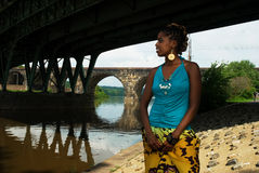 Lady stands under the bridge. African american gazing by the river stock image
