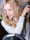 Lady straightening hair Stock Photo