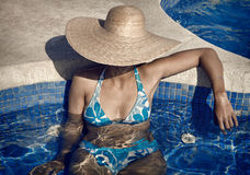 Lady with Straw Hat and Bikini in the Pool Stock Photos