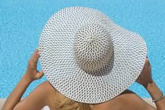 Lady with a straw hat looking at the swimming pool Royalty Free Stock Photo