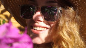 Lady in straw hat and sunglasses smiling on camera. Cheerful young lady in straw hat and sunglasses smiling on camera in blooming garden with flowers stock footage