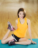 Lady Stretching. An Asian lady doing her warm up stretching exercise in a gym Royalty Free Stock Photos