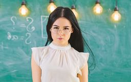Lady strict teacher on calm face stands in front of chalkboard. Woman with long hair in white blouse stands in classroom. Teacher with glasses looks at camera royalty free stock images