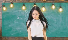 Lady strict teacher on calm face stands in front of chalkboard. Woman with long hair in white blouse stands in classroom. Teacher with glasses and waving hair royalty free stock photos