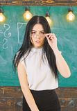 Lady strict teacher on calm face stands in front of chalkboard. Woman with long hair in white blouse stands in classroom. Strict teacher concept. Teacher with stock photos