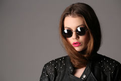 Lady in a studded leather jacket and circle sunglasses. Close up. White background Stock Photo