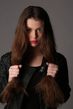 Lady in a studded leather jacket holding her hair. Close up. White background Royalty Free Stock Photography