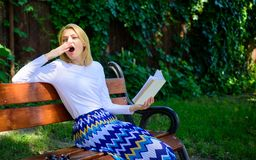Lady student read boring literature outdoors. Boring literature. Woman yawning blonde take break relaxing in garden. Reading book. Girl sit bench relaxing with stock photos