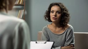 Lady suffering anxiety, discussing her issues with female expert in psychiatry stock photography