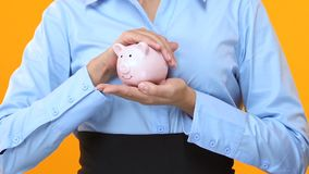 Lady in suit holding piggy bank, value-enhancing investments, profitable project
