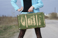Lady and suitcase. Lady and and green shabby ancient suitcase royalty free stock photo