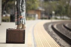 A lady with a suitcase. A lady waiting at the railway station with a retro suitcase Stock Photography