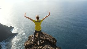 Young woman raising her arms on beautiful steep cliff over the ocean. Lady on the summit in beautiful scenery. stock footage