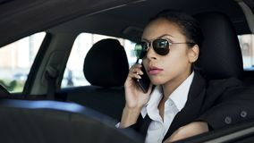 Lady in sunglasses sitting in car and talking on cellphone, police agent on duty stock image