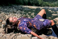 A lady is sunning on the beach of a mountain river. Rest of a woman against a beautiful nature. The lady lies under the sun and rests. Rest of woman in nature Royalty Free Stock Image