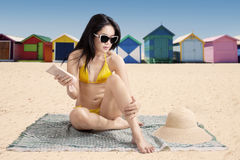 Lady with sunscreen and the beach cottage. Young asian lady wearing swimsuit while sitting at beach and using suntan lotion with the background of the beach stock image