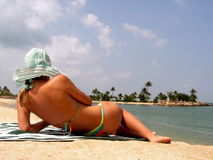 Lady suntanning on beach. Resort living with sun tanning. Relaxation at its best. Reading in the sun with a sunhat. Lady is reclining to her left side Stock Image