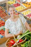 Lady in supermarket holding basket vegetables Royalty Free Stock Photos