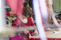 Lady Tailor Working on Cloth on a Cutting Table stock images