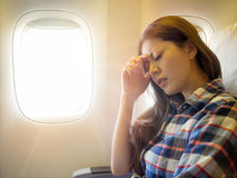 Lady take the plane feeling painful for head. Wearing casual style clothes lady take the plane feeling painful for head and hand putting on forehead express royalty free stock images
