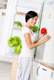 Lady takes red pepper from opened fridge Stock Images
