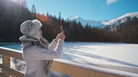 Lady is Taking Picture in Mountains in Winter by SmartPhone with Sun Lense Flare. Young Slender Lady is Taking Picture in Mountain Lake in Winter by SmartPhone stock video