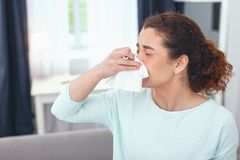 Lady taking a sick leave due to having seasonal allergies. Achoo once more. Lady on a sick leave staying at home and having a runny nose as a result of suffering Stock Photo