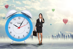 Lady talking on cell phone with big alarm clock Royalty Free Stock Image