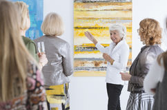 Lady talking about painting. Elegantly dressed older lady talking about painting during its premiere Royalty Free Stock Photos