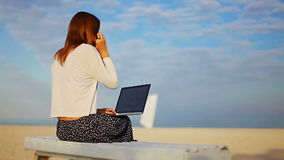 Lady talking on the phone with a laptop on his knees, sitting on a sandy beach stock video