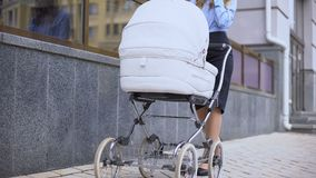Lady talking phone walking with baby carriage near business center, multitasking. Stock footage stock video