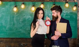 Lady teacher and strict schoolmaster care about discipline and rules in school. Man with beard hold book and girl. Teacher holds alarm clock, chalkboard on royalty free stock photos
