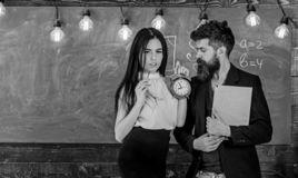 Lady teacher and strict schoolmaster care about discipline and rules in school. Man with beard hold book and girl. Teacher holds alarm clock, chalkboard on stock image