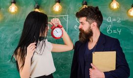 Lady teacher and strict schoolmaster care about discipline and rules in school. School rules concept. Man with beard. Hold book and girl teacher holds alarm stock photos