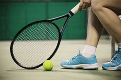 Lady tennis player sitting in the court during game break stock photo