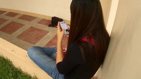 Lady text messaging by smartphone. San Pablo City, Laguna, Philippines - September 9, 2015: Young lady spends lots of her time texting with her smartphone stock footage