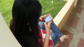 Lady text messaging by smartphone. San Pablo City, Laguna, Philippines - September 9, 2015: Young lady spends lots of her time texting with her smartphone stock video footage