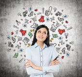 Lady is thinking about shopping. Colourful shopping icons are drawn on the concrete wall. Royalty Free Stock Photography