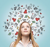 Lady is thinking about shopping. Colourful shopping icons are flying in the air. Royalty Free Stock Photos