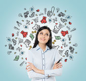 Lady is thinking about shopping. Colourful shopping icons are flying in the air. Royalty Free Stock Images
