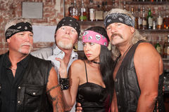 Lady with Three Tough Men. Sexy lady with 3 tough motorcycle gang members in bar Stock Photo