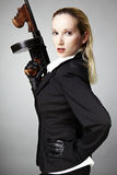 Lady with tommy gun. Mafia style fashion studio portrait - nice young woman posing with Tommy gun for figure and portrait photos in retro criminal style royalty free stock photography