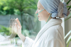 Lady touching glass. Young lady with tumor touching the hospital window glass Royalty Free Stock Photo