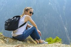 Lady tourist with backpack. Sitting on a rock on the top of mountain and admire the view near the Transfagarasan road stock images