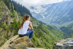 Lady tourist sitting on mountain Stock Images