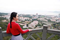 Lady tourist standing on a rock on the top of mountain and admire the view , Xiamen, China. Lady tourist standing on a rock on the top of mountain and admire the stock photos