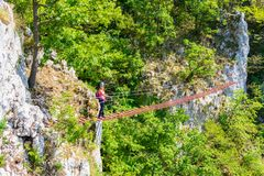 Lady tourist on suspended wooden via ferrata bridge on a route called `Casa Zmeului` in Vadu Crisului, Padurea Craiului mountains. Apuseni, Romania, on a stock photography